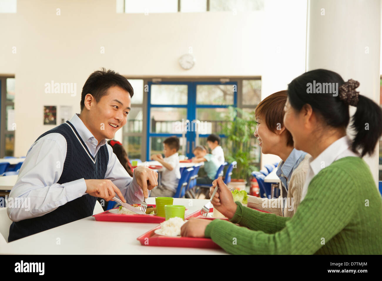 Teachers talking at lunch in school cafeteria - Stock Image