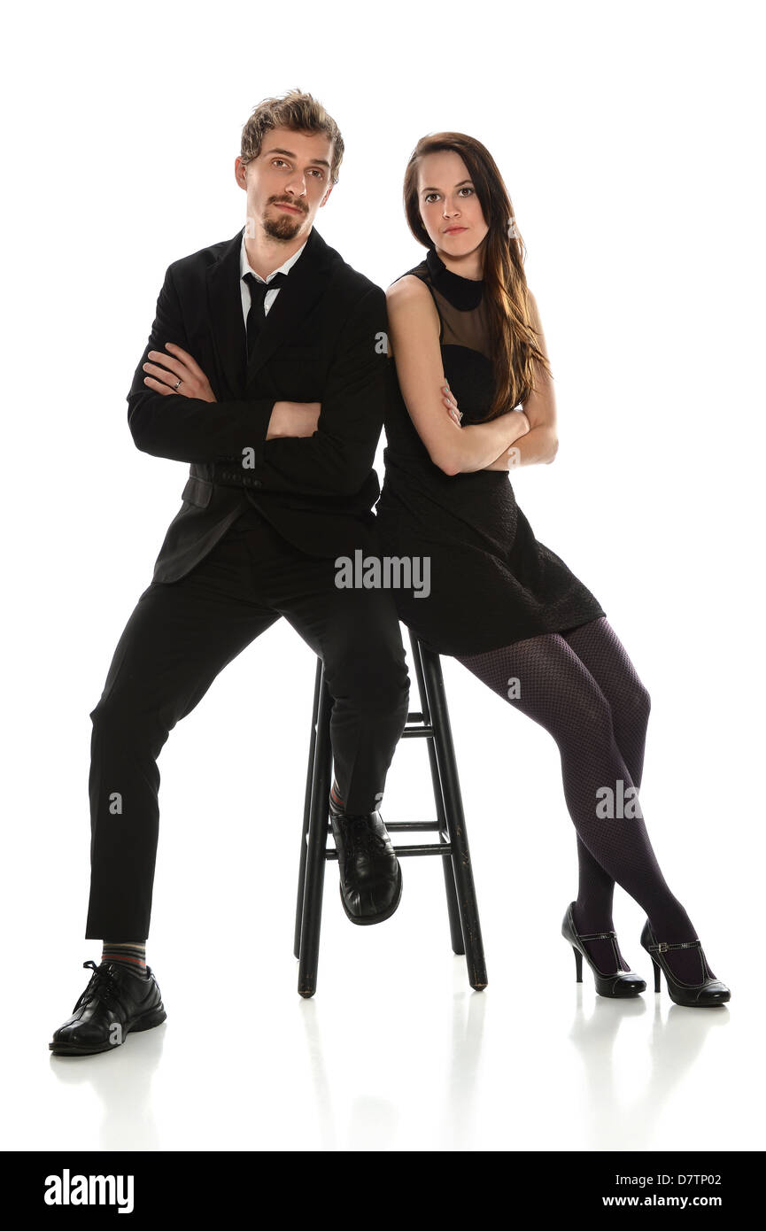 Young couple with serious expressions seating isolated over white background - Stock Image