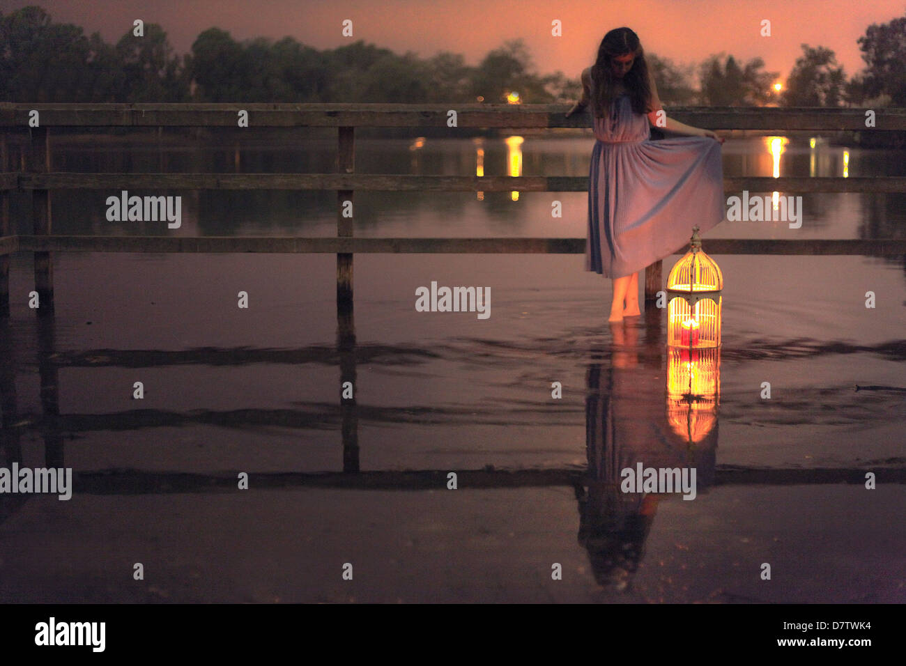 Girl standing in ripples of water with a birdcage that has a