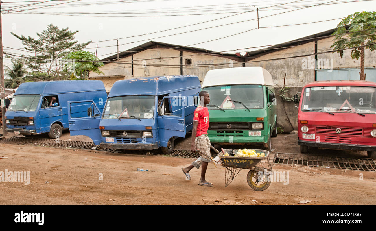 A Nigerian boy pulls his wheelbarrow in the street of Lagos. - Stock Image