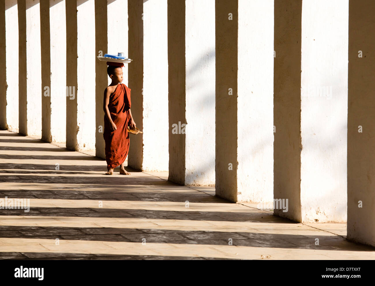 Novice Buddhist monk standing in the shadows of columns at Shwezigon Paya, Nyaung U, Bagan, Burma Stock Photo