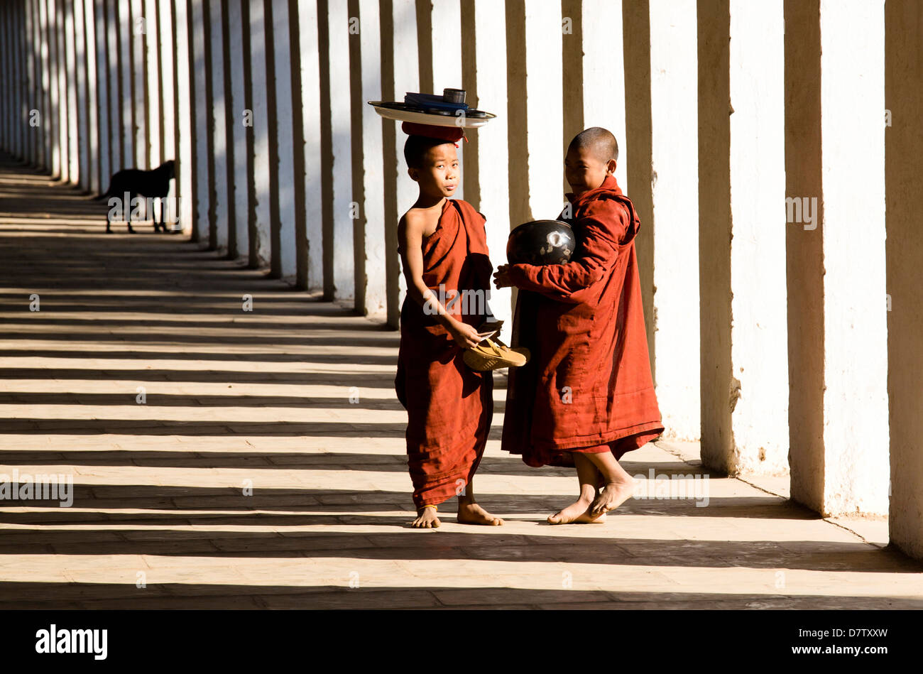 Novice Buddhist monks collecting alms, standing in the shadows of columns at Shwezigon Paya, Nyaung U, Bagan, Burma Stock Photo