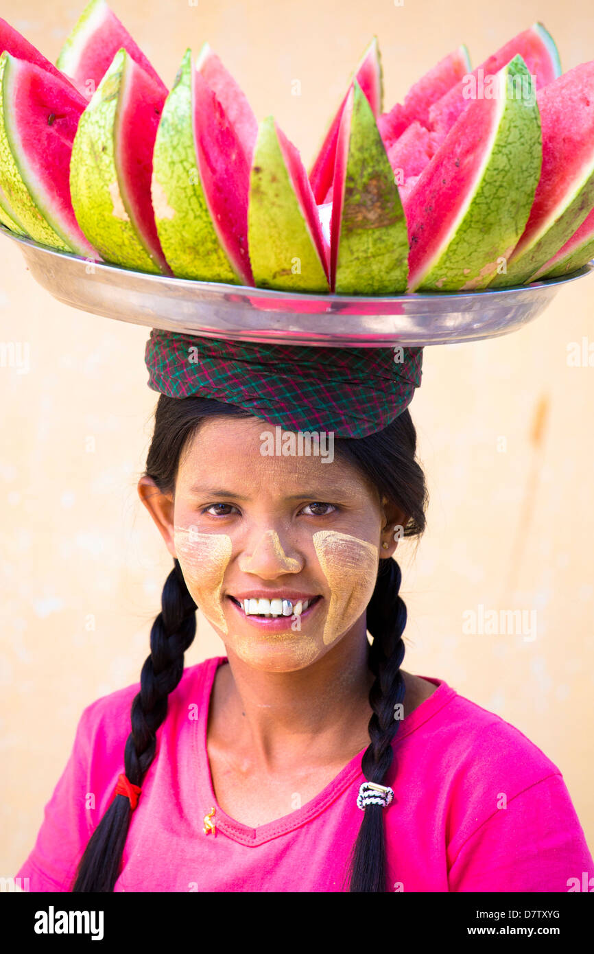 Local woman with Thanakha traditional face painting, carrying a tray of watermelon on her head, Shwezigon Paya, Stock Photo
