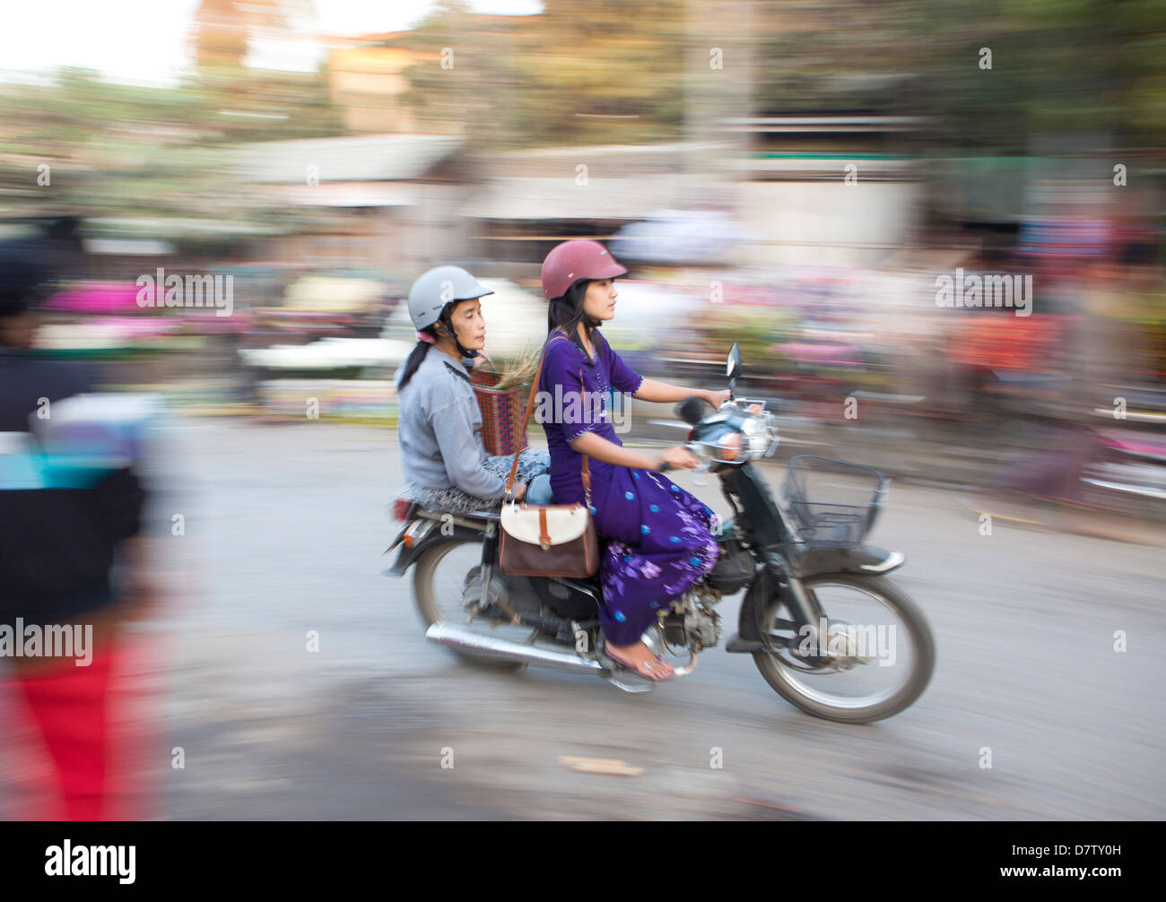 Panned and blurred shot, creating a sense of movement, of two women riding moped through a market, Mandalay, Burma - Stock Image
