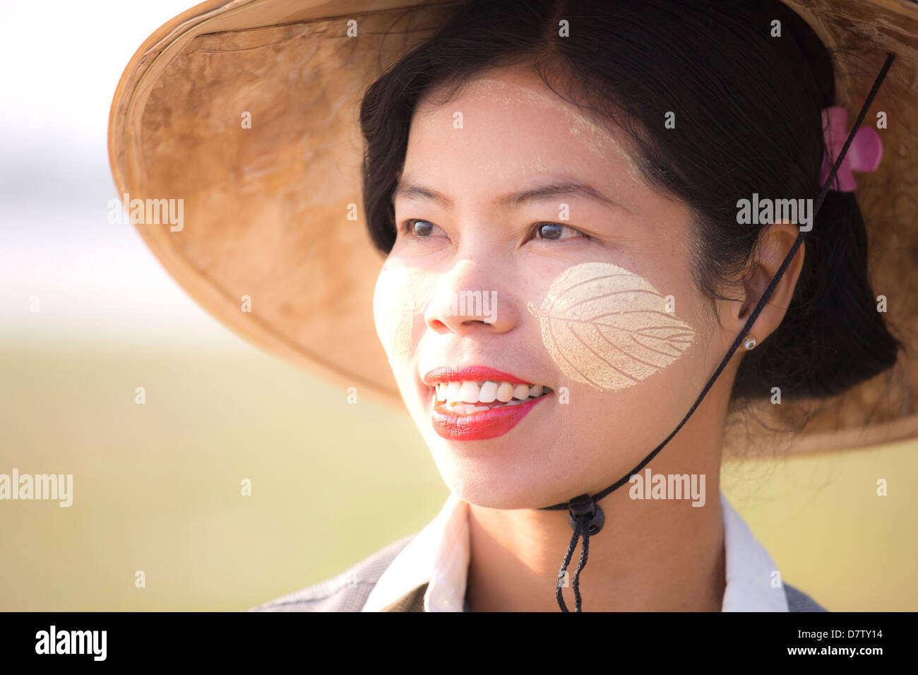 Backlit portrait of local woman wearing traditional clothing, near Mandalay, Burma - Stock Image