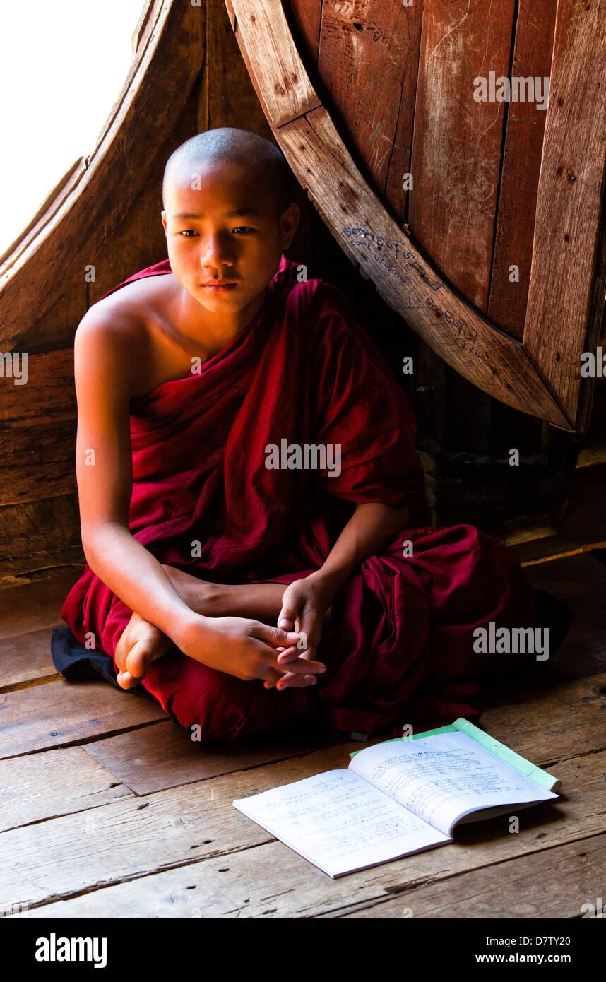 Novice Buddhist monk in lesson at Shwe Yaunghwe Kyaung, a famous teak monastery, Nyaungshwe, Inle Lake, Shan State, - Stock Image