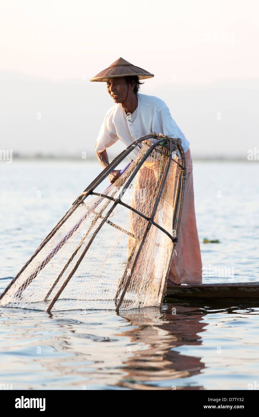 Intha leg rowing fishermen at sunset on Inle Lake, Inle Lake, Shan State, Burma - Stock Image