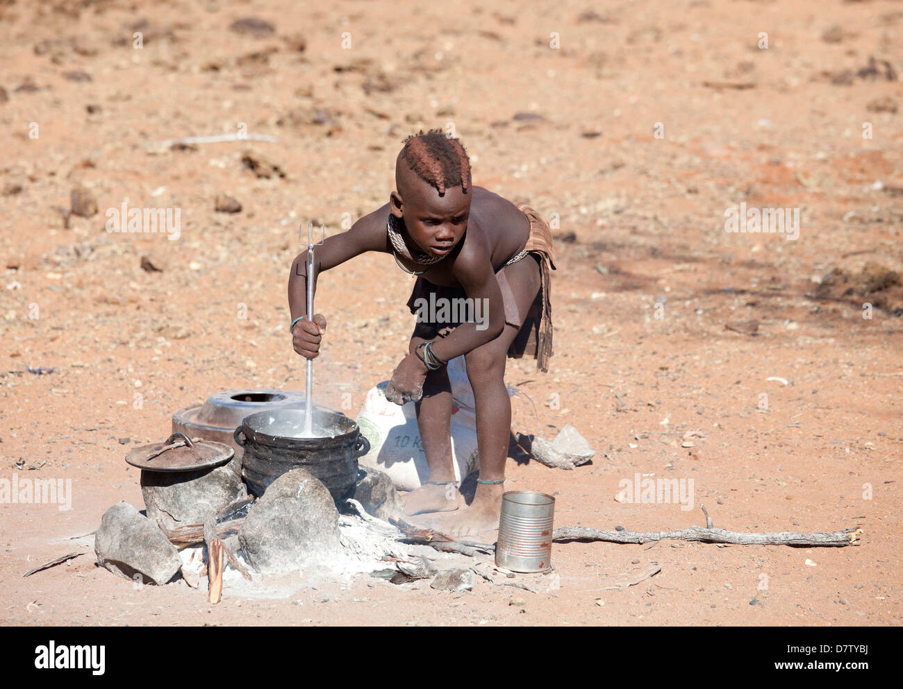 Young Himba boy cooking food on open fire in his village, Kunene Region (formerly Kaokoland) in the far north of Stock Photo