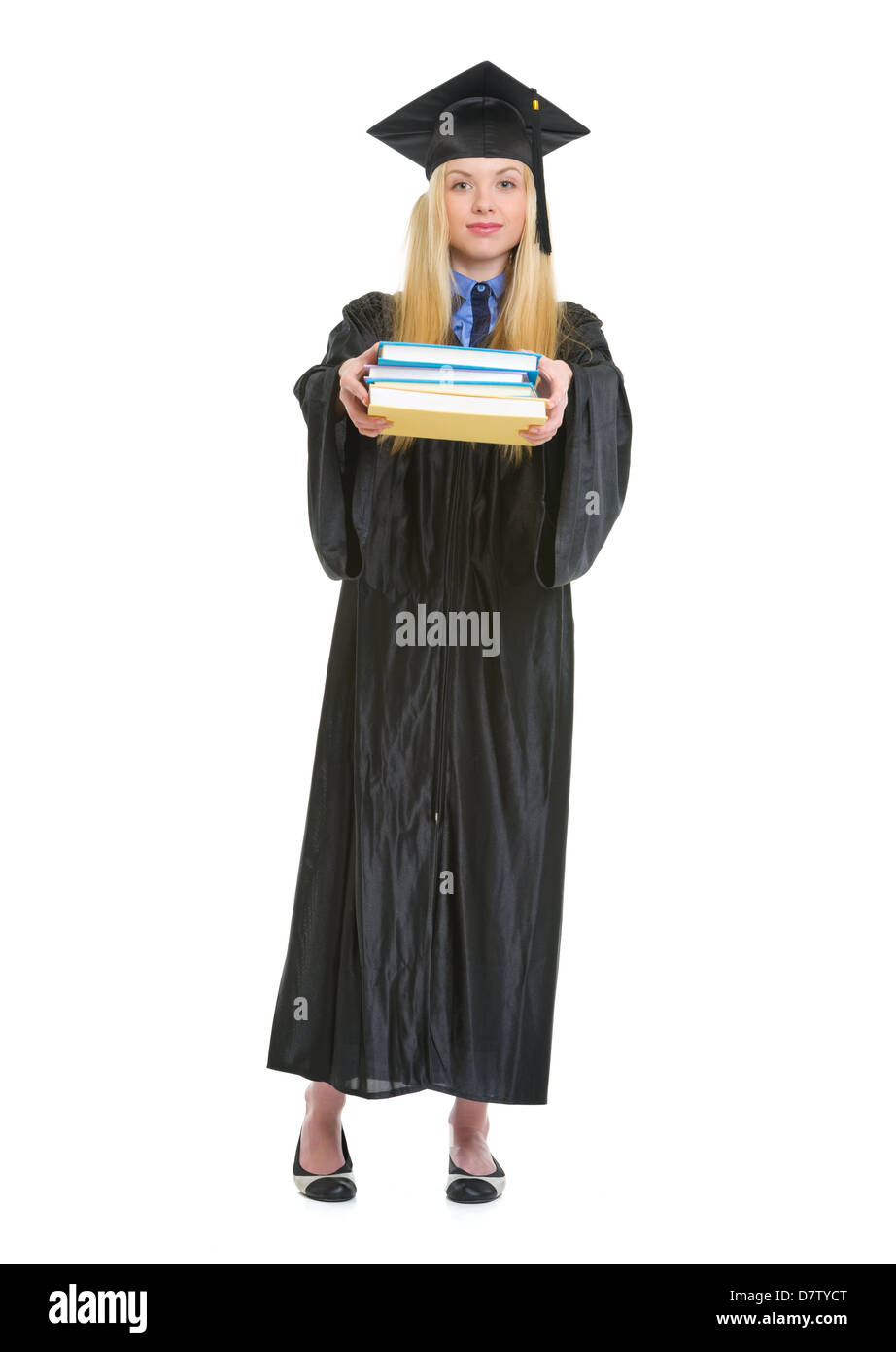 Full length portrait of young woman in graduation gown giving books ...