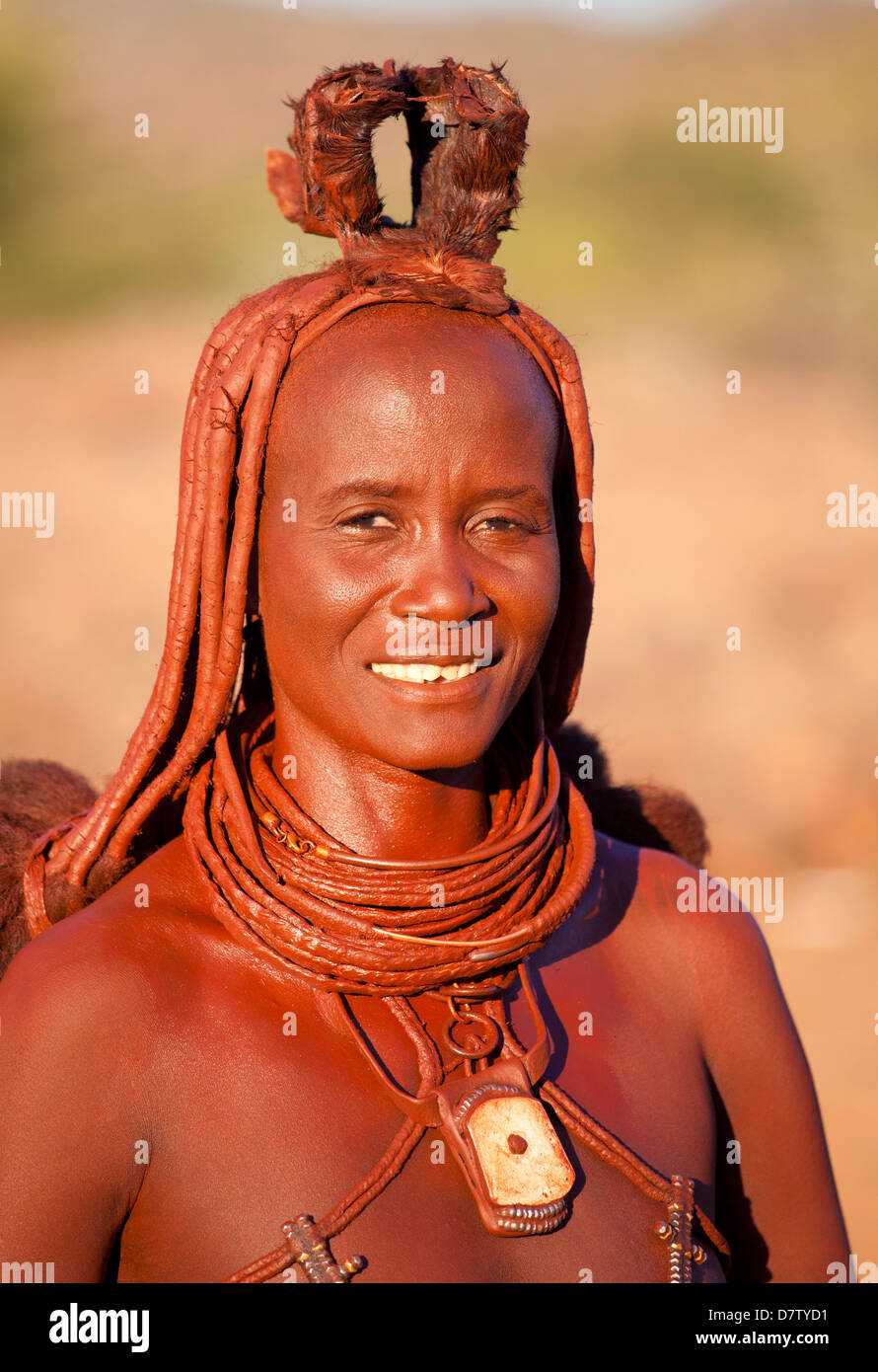 Himba woman inside a mud dwelling hut wearing dress and jewellery and covered in Otjize, Kunene Region, Kaokoland, - Stock Image