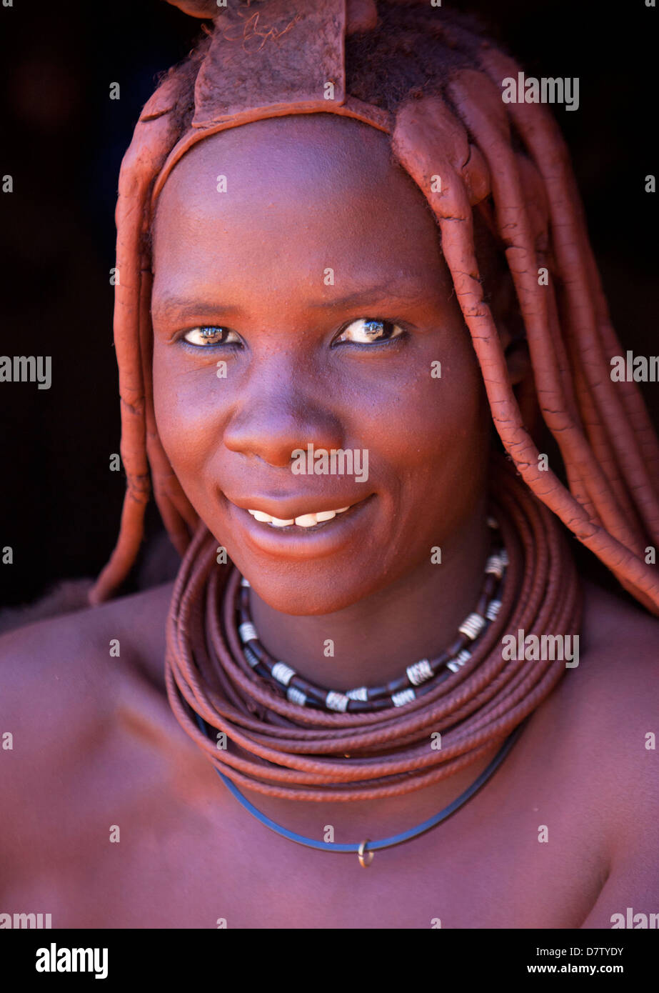 Himba woman wearing traditional dress with her skin covered in Otjize, Kunene Region, Kaokoland, Namibia - Stock Image