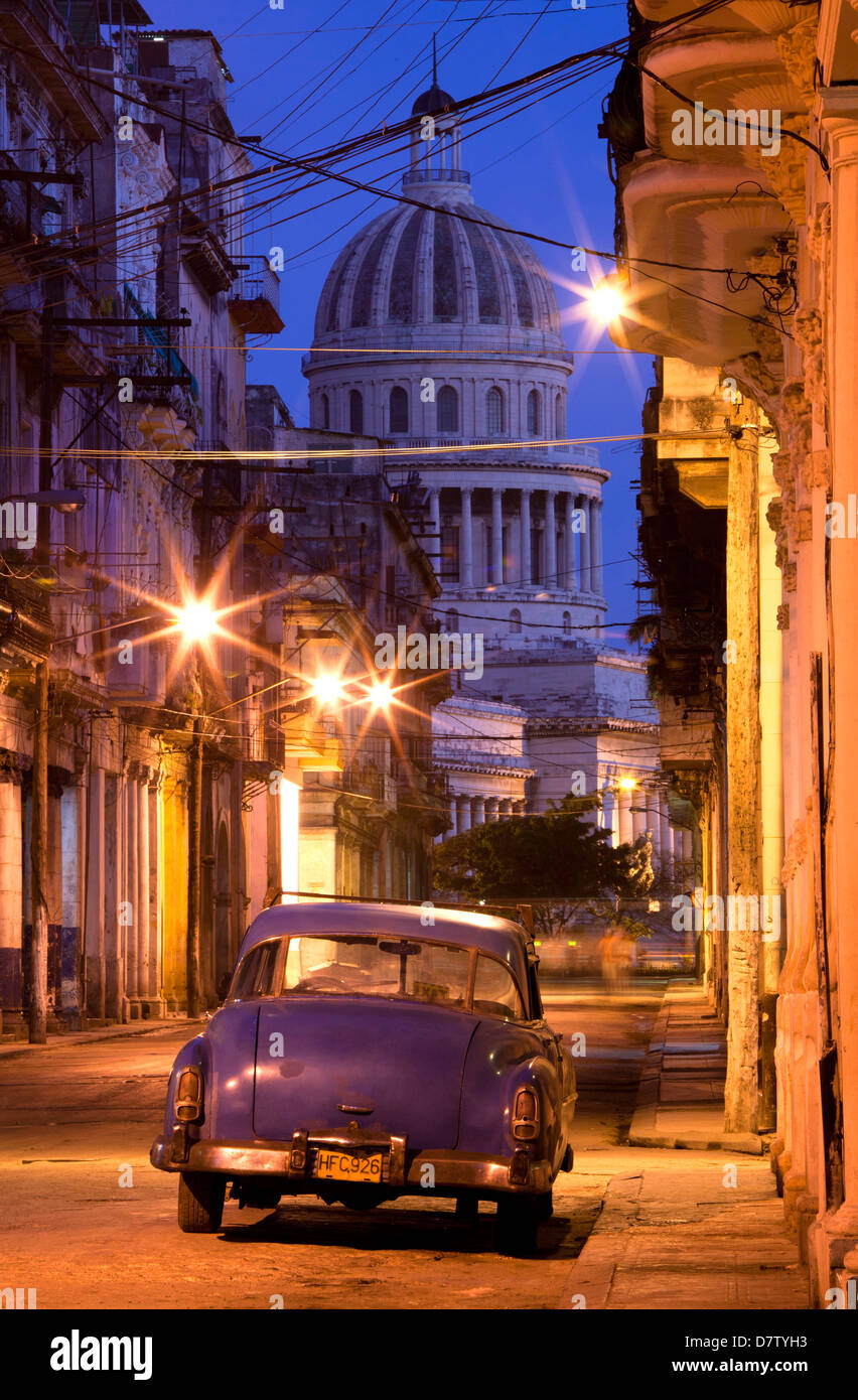 Vintage American car parked on floodlit street with The Capitolio in the background, predawn, Havana Centro, Cuba, Stock Photo