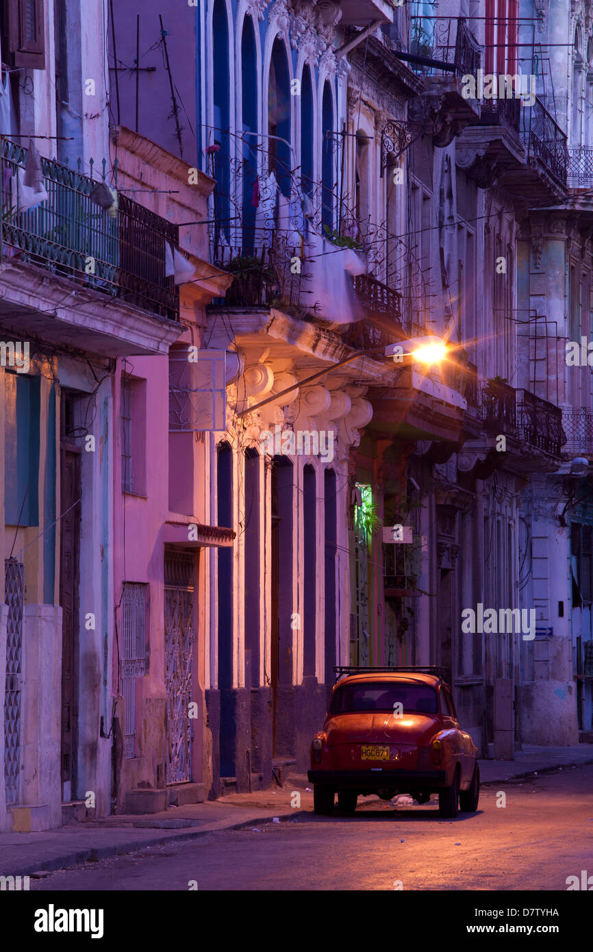 Vintage American car parked on floodlit street, predawn, Havana Centro, Cuba, West Indies - Stock Image