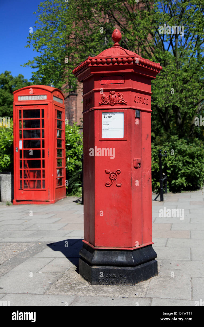 Red Victorian pillar box with red Giles Gilbert Scott telephone kiosk in the background, Abbey Foregate, Shrewsbury - Stock Image