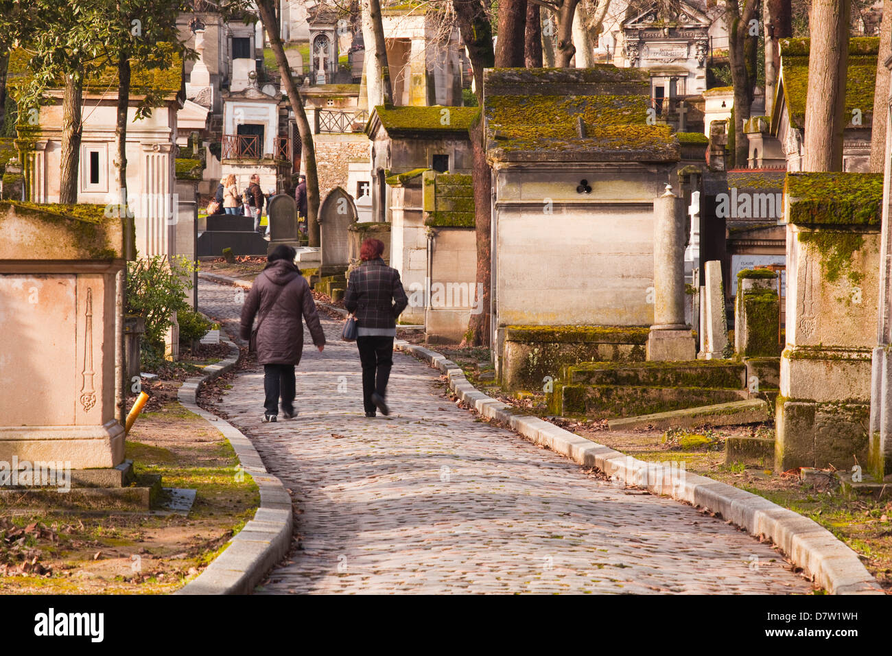 People walking past the gravestones of Pere Lachaise cemetery, Paris, France - Stock Image