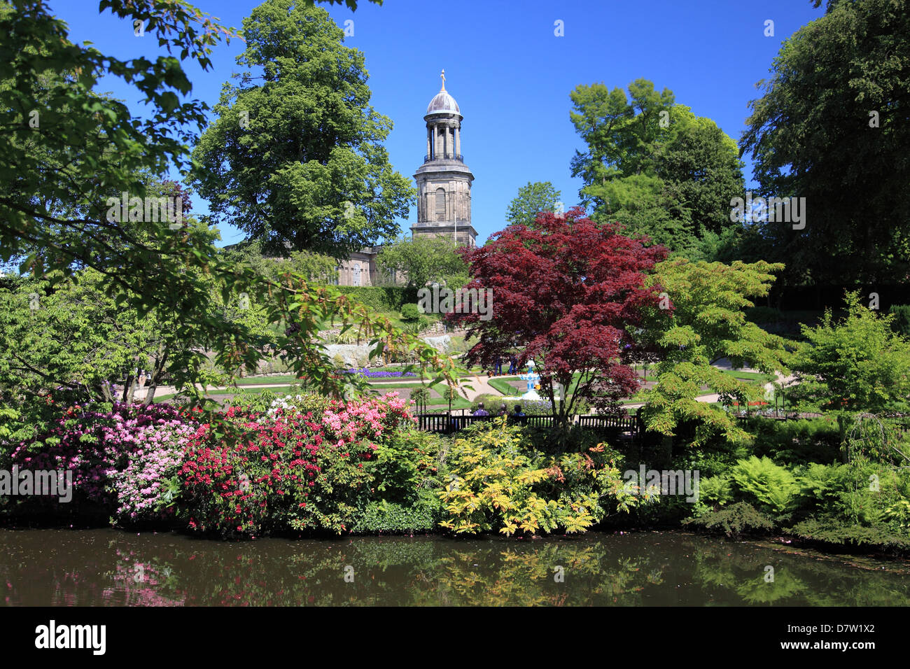 The Dingle, a garden within the Quarry Park in Shrewsbury, with the church of St. Chad in the background. - Stock Image