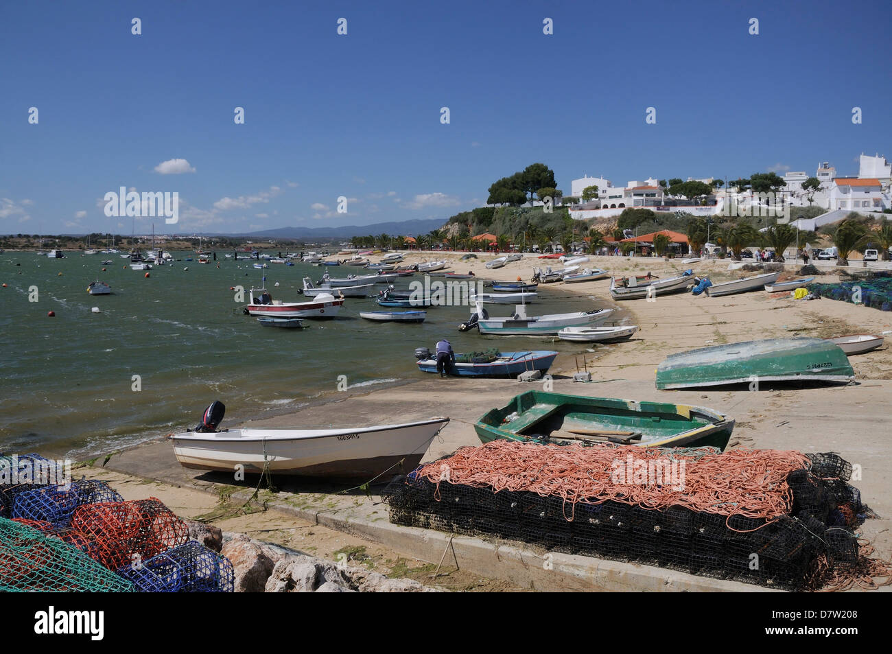 Lobster pots on quayside next to moored fishing boats, Alvor, near Portimao, Algarve, Portugal - Stock Image