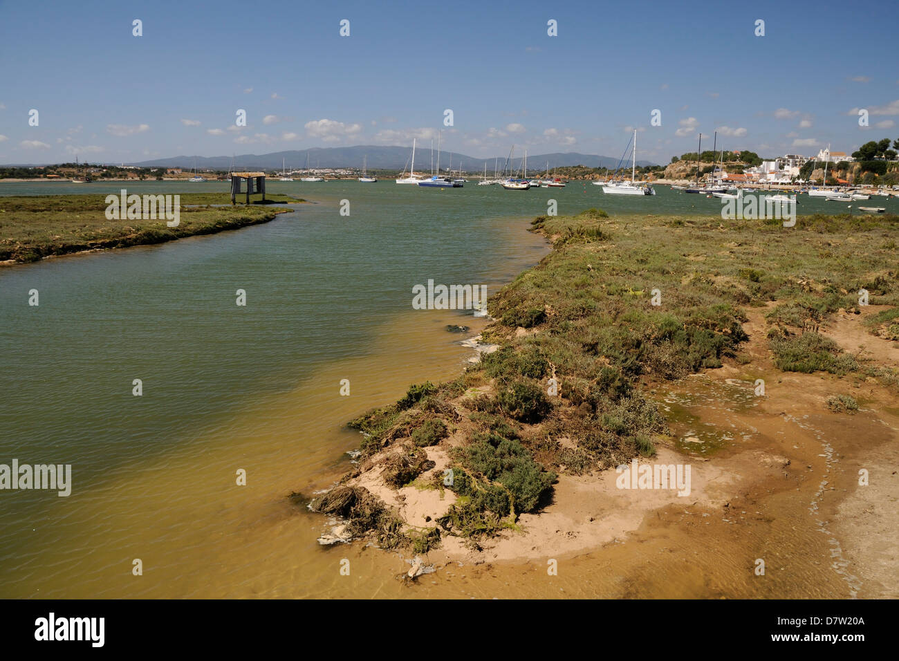 Saltmarsh, estuarine harbour at high tide and moored sailing yachts, Alvor, near Portimao, Algarve, Portugal - Stock Image