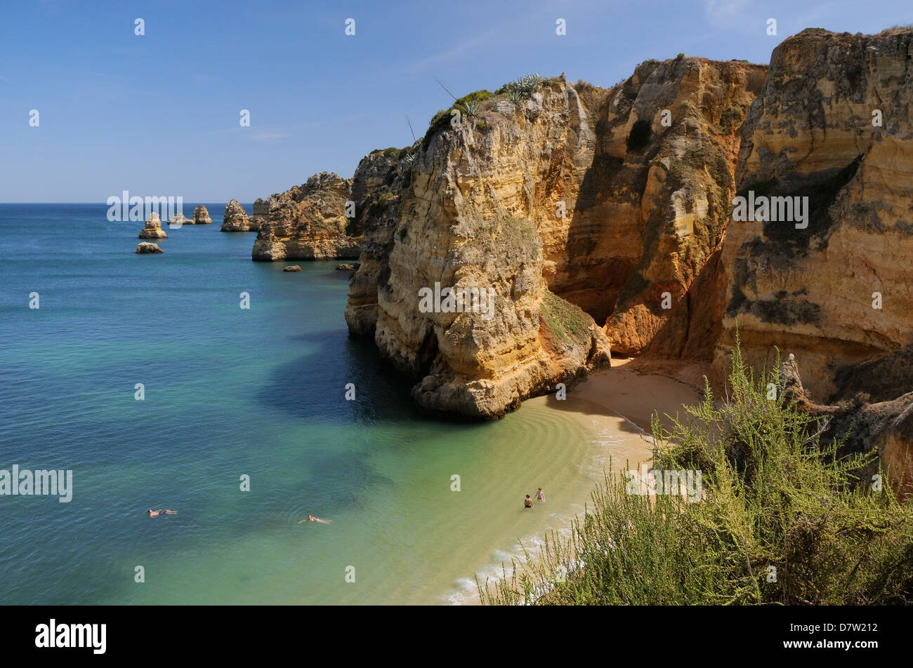 Weathered sandstone cliffs and sea stacks at Praia Dona Ana, Lagos, Algarve, Portugal - Stock Image
