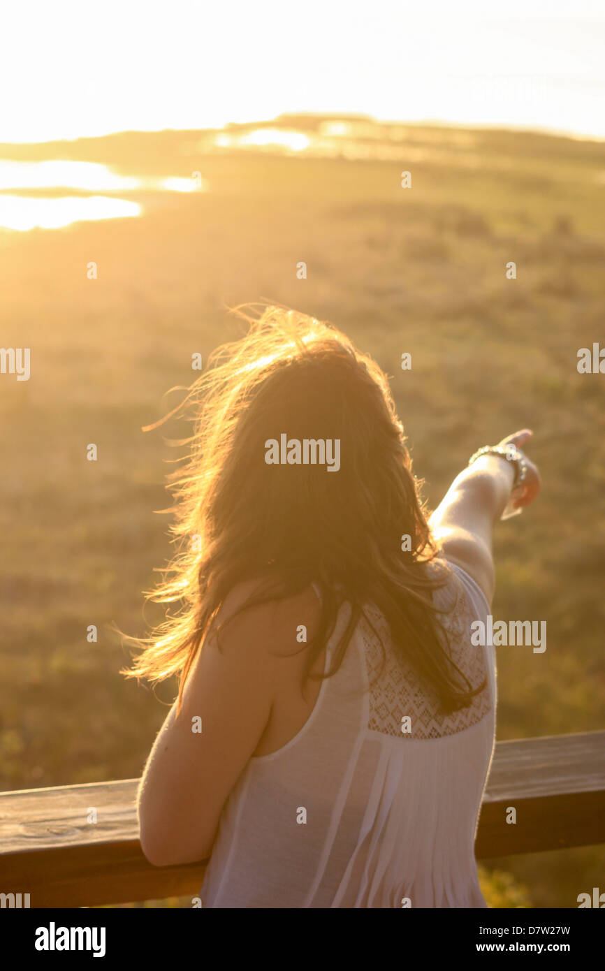 A young woman points out to a water hole at sunset, St. Lucia Wetlands, Kwa-Zulu Natal, South Africa - Stock Image