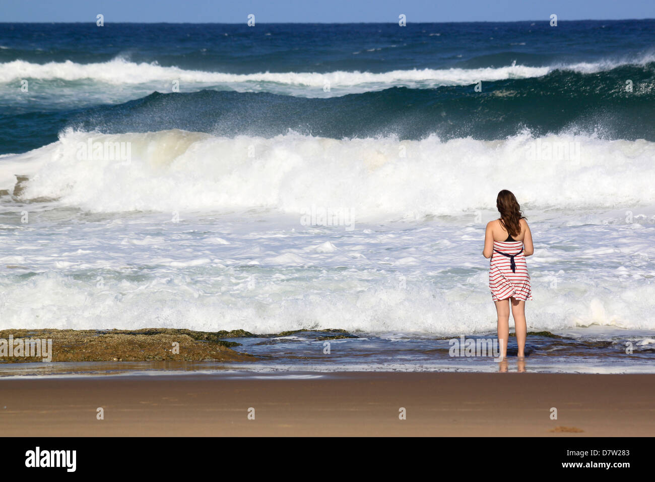 A young woman stands by crashing waves at the beach, St. Lucia Wetlands, Kwa-Zulu Natal, South Africa - Stock Image