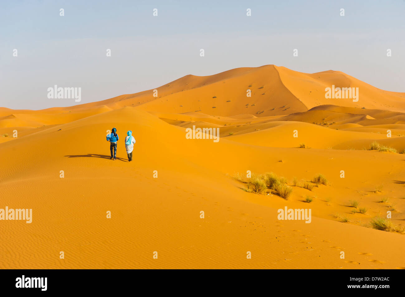 Two Berber men walking in the sand dunes of Erg Chebbi Desert, Sahara Desert near Merzouga, Morocco, North Africa Stock Photo