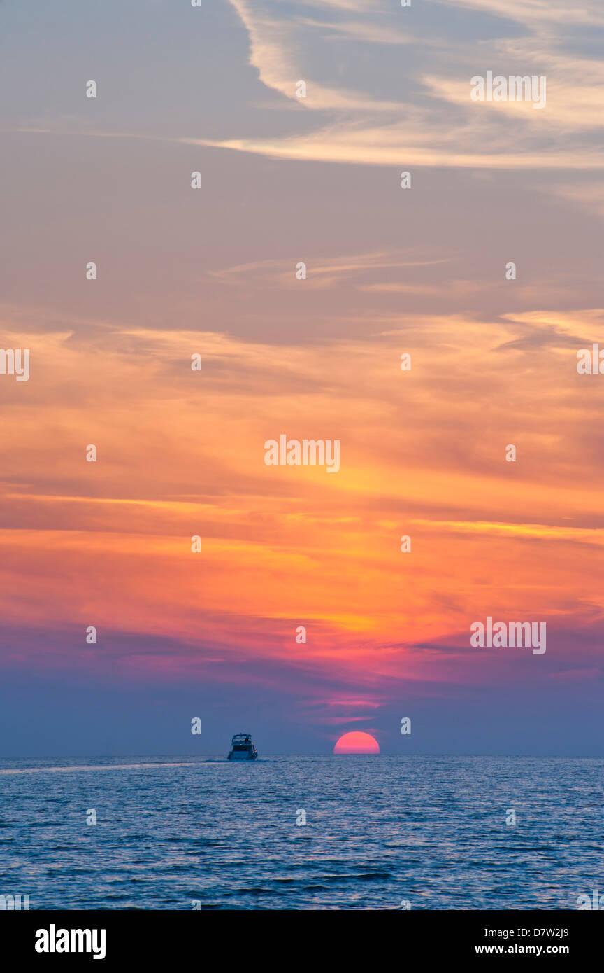 Boat driving into the sunset at Zlatni Rat Beach, Bol, Brac Island, Dalmatian Coast, Adriatic, Croatia - Stock Image