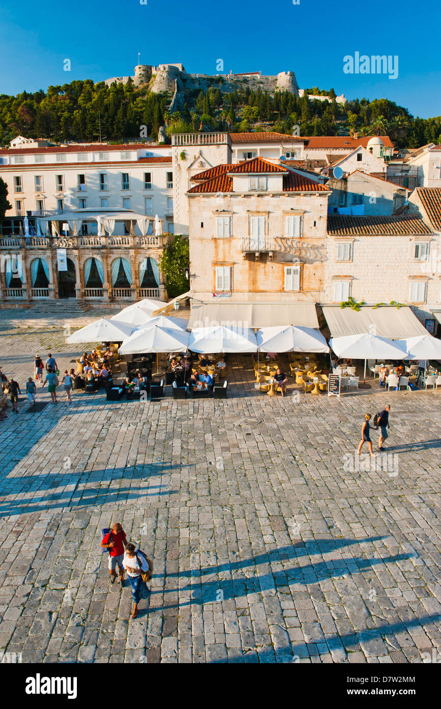 Tourists in St. Stephens Square, with the Spanish Fort (Fortica) above, Hvar Town, Hvar Island, Dalmatian Coast, - Stock Image