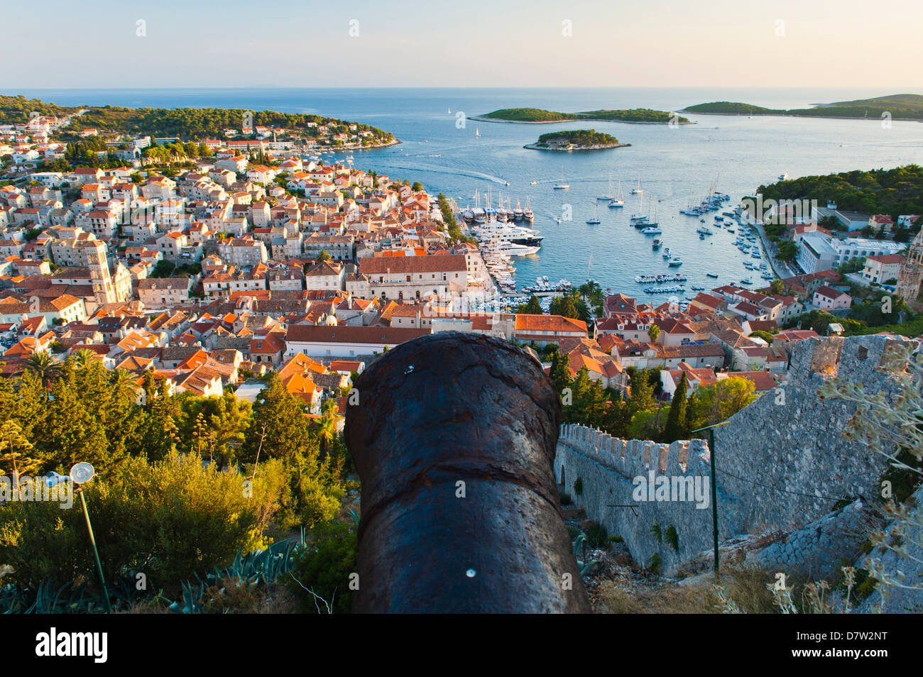 Hvar Fortress cannon and Hvar Town at sunset taken from the Spanish Fort, Hvar Island, Dalmatian Coast, Adriatic, - Stock Image
