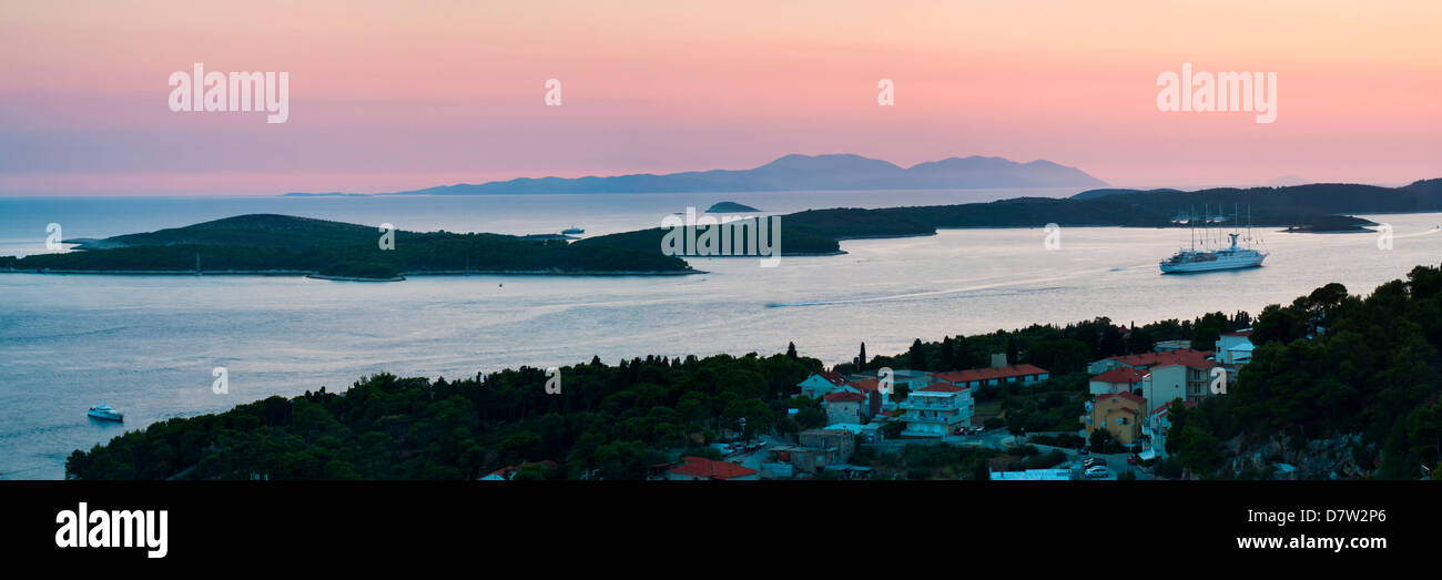 Pakleni Islands and Vis Island, a cruise ship moored at sunset, seen from Hvar Island, Dalmatian Coast, Adriatic - Stock Image