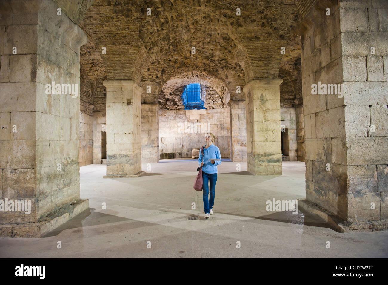 Tourist exploring the underground halls at Diocletian's Palace, UNESCO World Heritage Site, Split, Dalmatian - Stock Image