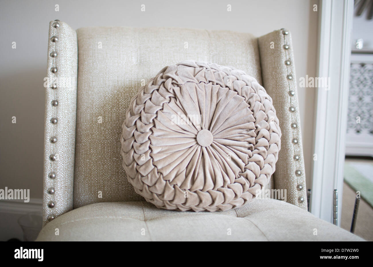 An ornate pleated or ruched cushion sitting on a chair. - Stock Image