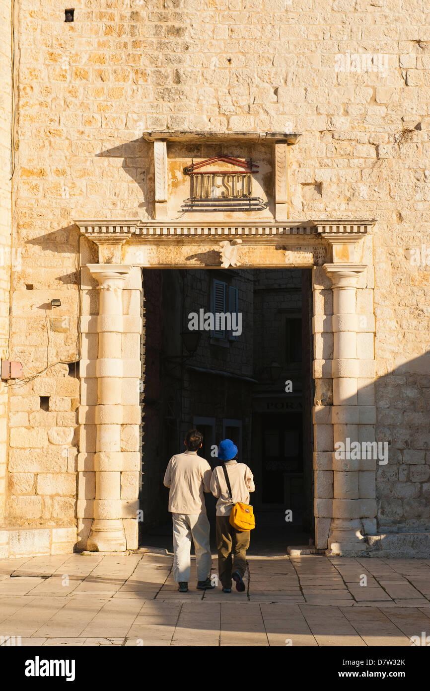 Tourist entering Old Town of Trogir through the South Town Gate, Trogir, UNESCO World Heritage Site, Dalmatian Coast, - Stock Image