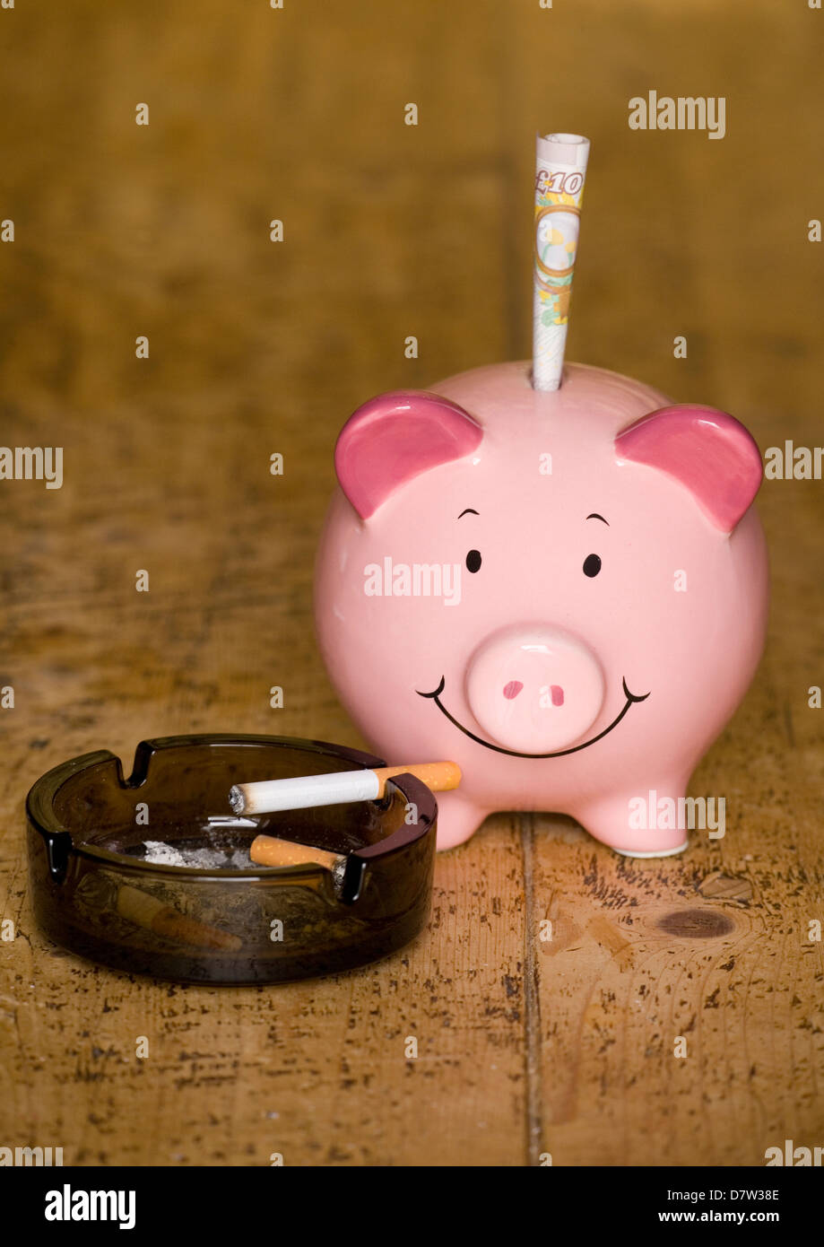 piggy bank and cigarettes on a wooden table - Stock Image