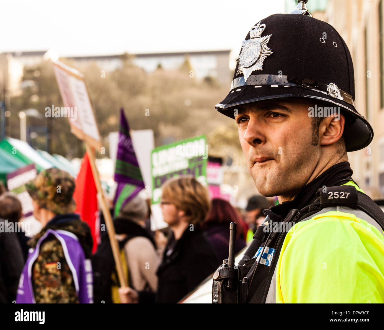People protest against the coalition Government cuts as a policeman looks on. - Stock Image