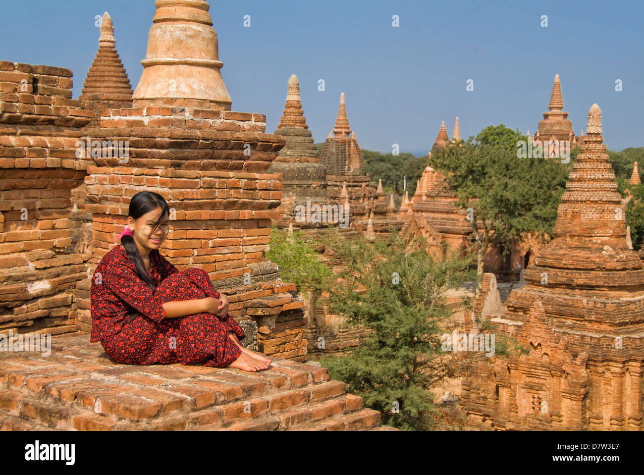 Young Burmese woman in a red dress sitting on the roof of a temple, Bagan (Pagan), Burma Stock Photo
