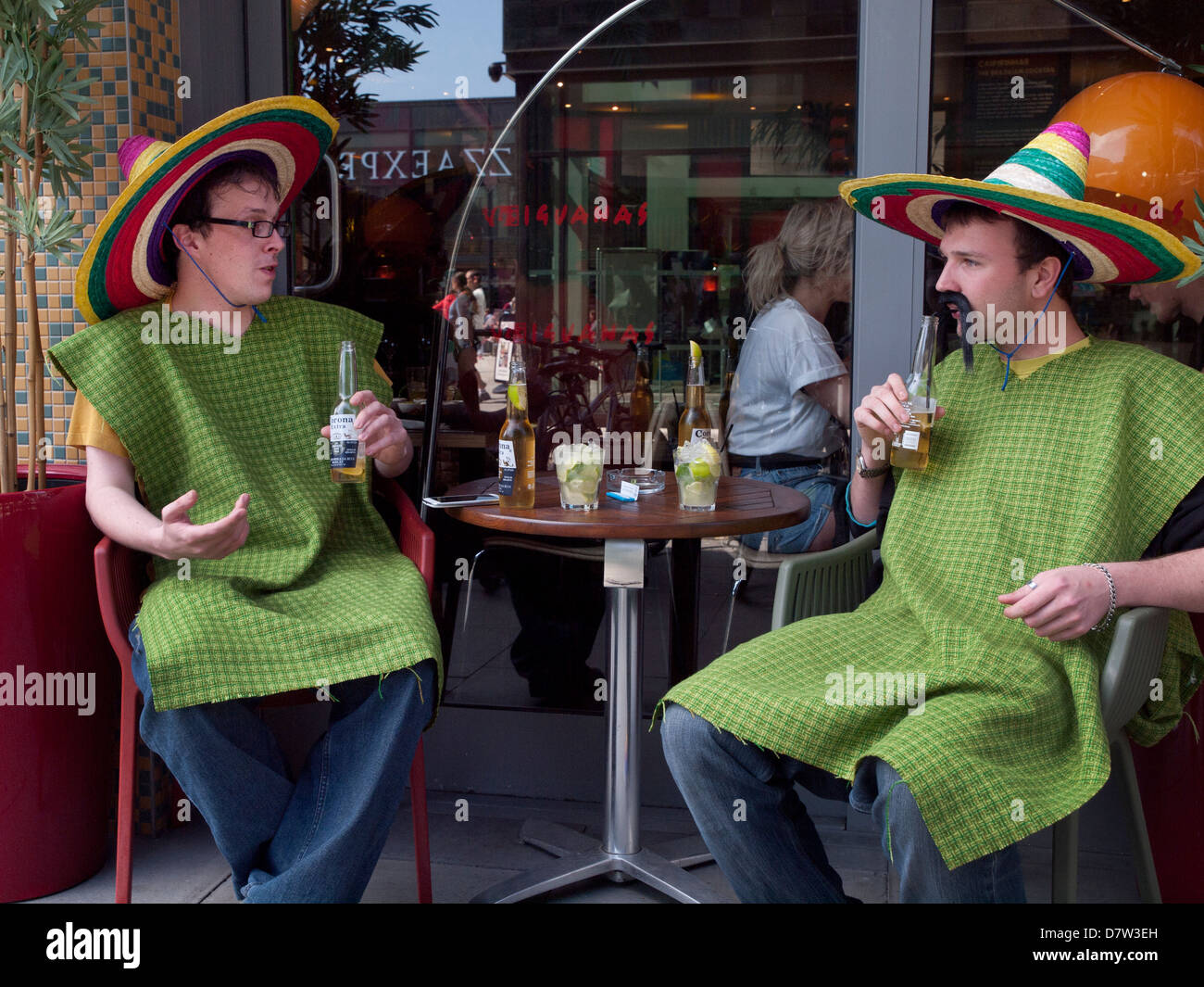 Men enjoying a beer, dressed as Mexicans - Stock Image