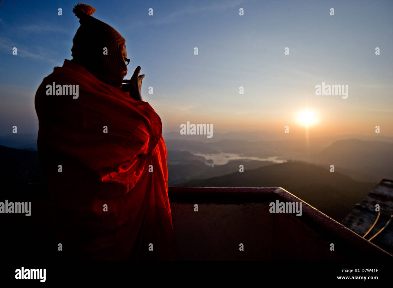 A monk looks out over a sunrise from the top of the sacred mountain Sri Pada (Adam's Peak), Sri Lanka - Stock Image