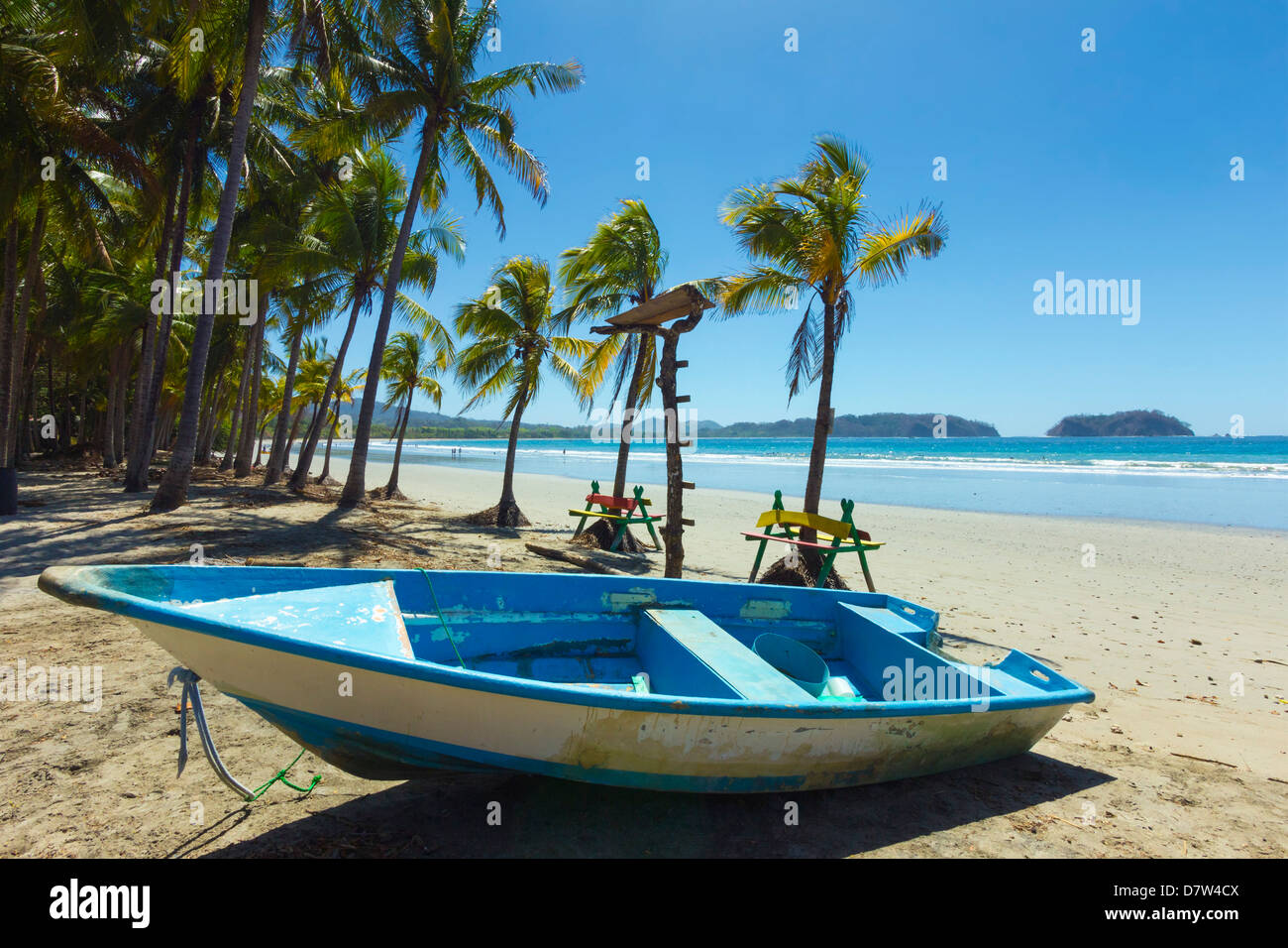 Boat on the palm-fringed beach at this laid-back village & resort, Samara, Guanacaste Province, Nicoya Peninsula, - Stock Image