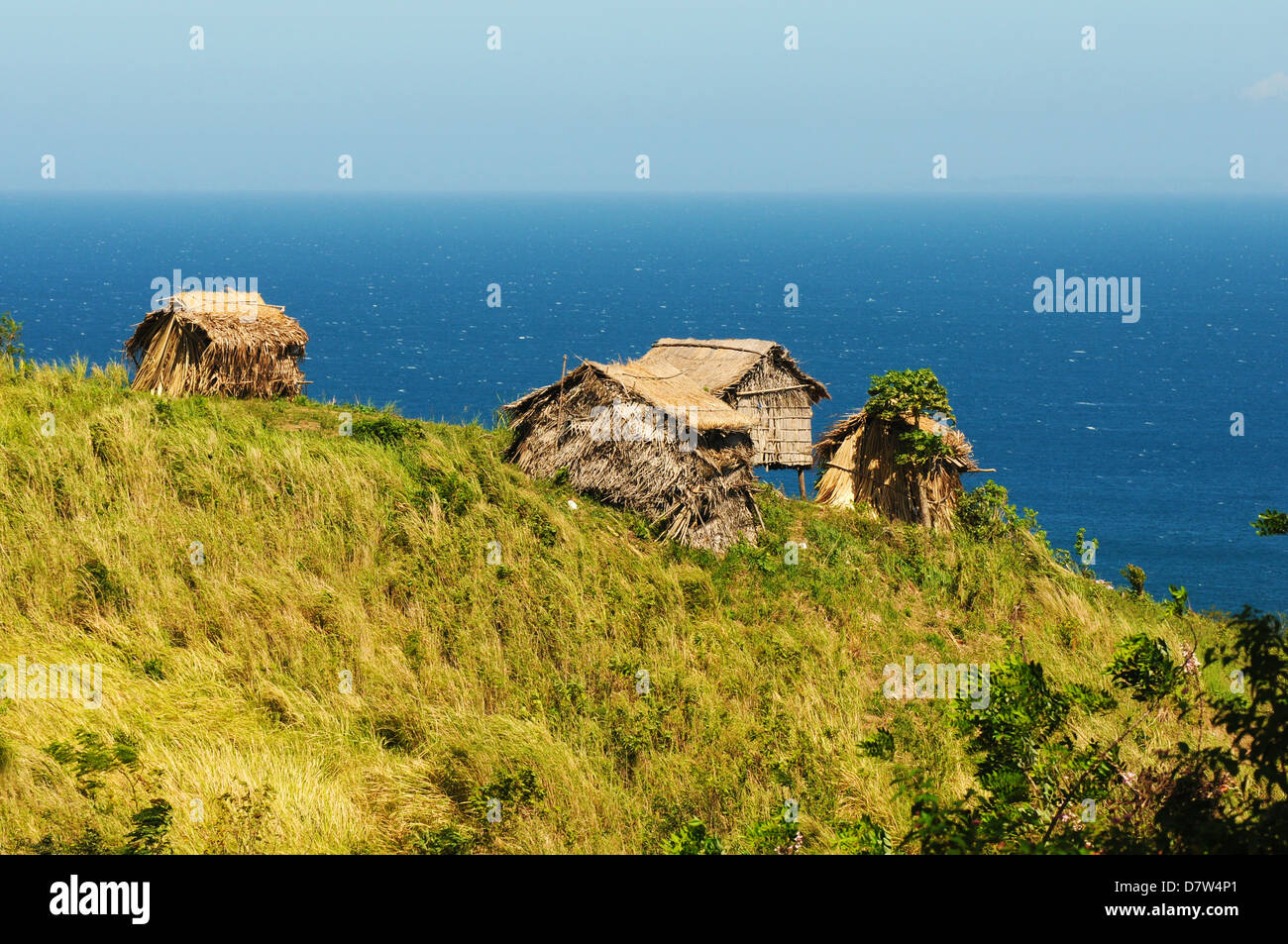 Green hills and Mangyan's huts at the Pacific ocean coast. Sunny weather over Mindoro Island, Philippines - Stock Image