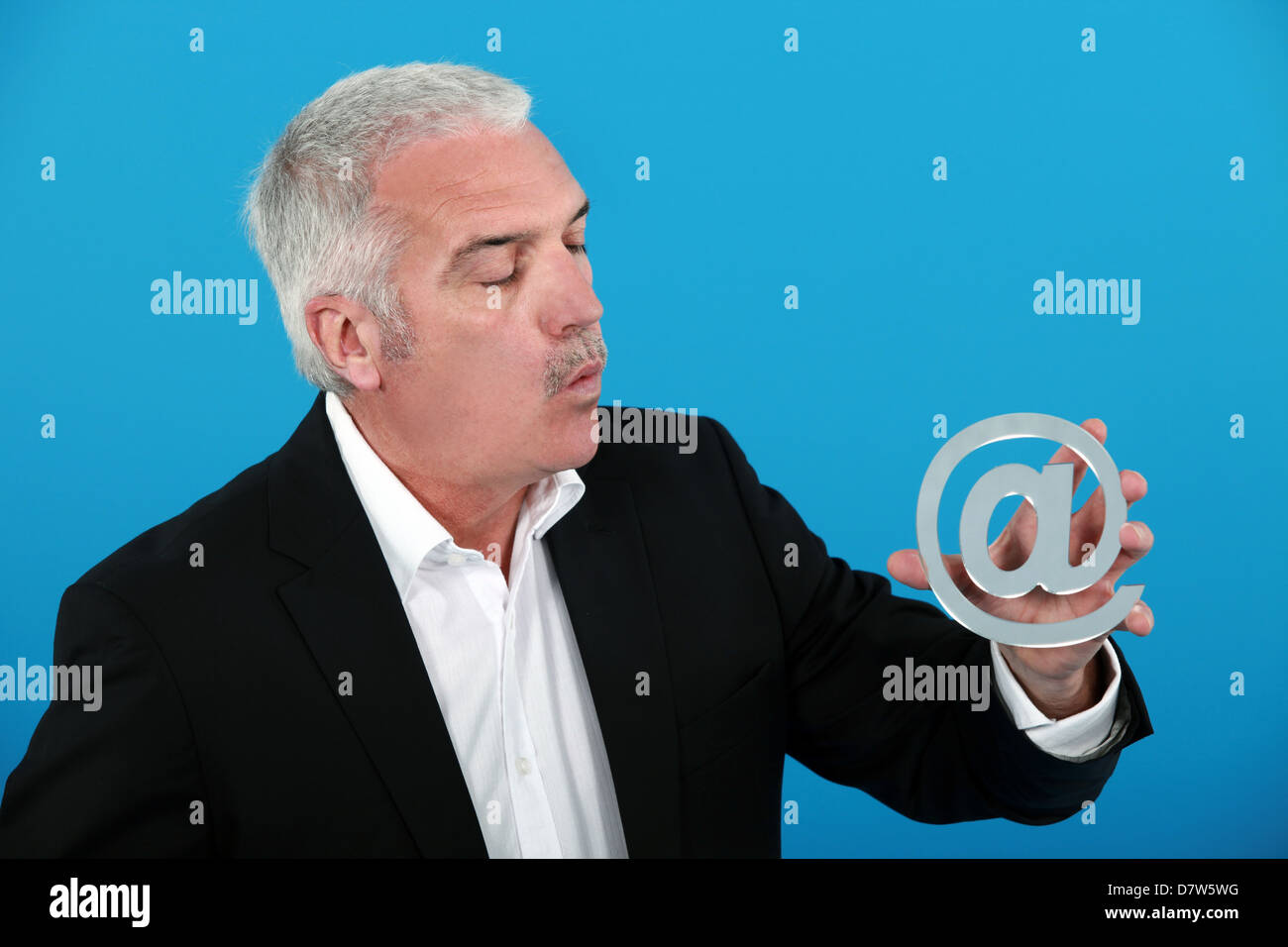Man holding an @ sign - Stock Image