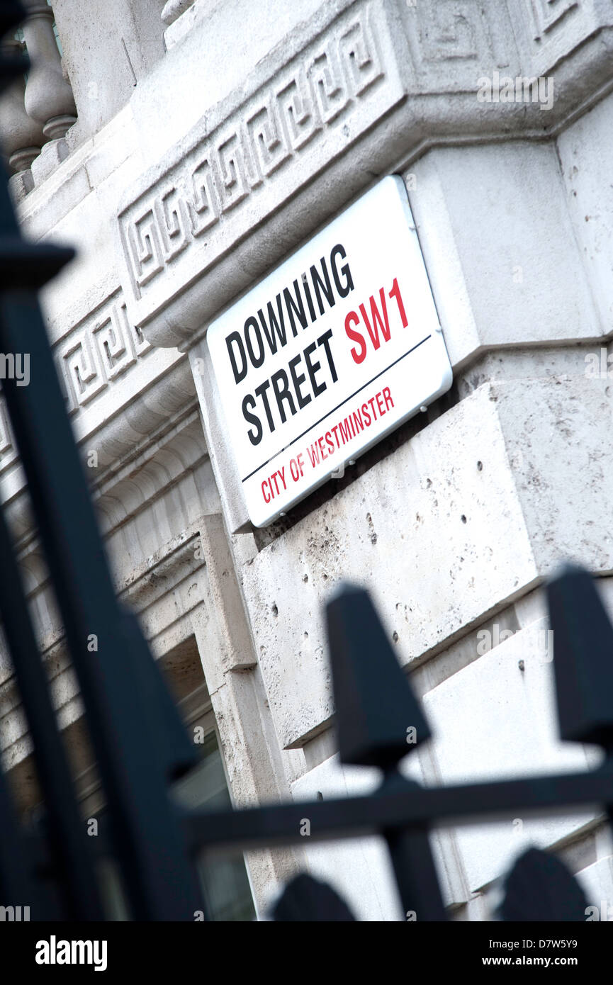Road sign on wall signifying Downing Street with railings in foreground - Stock Image