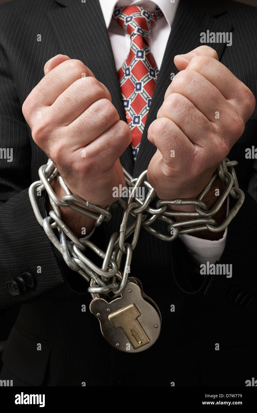 Close up of businessmans hands tied in heavy chains with padlock - Stock Image