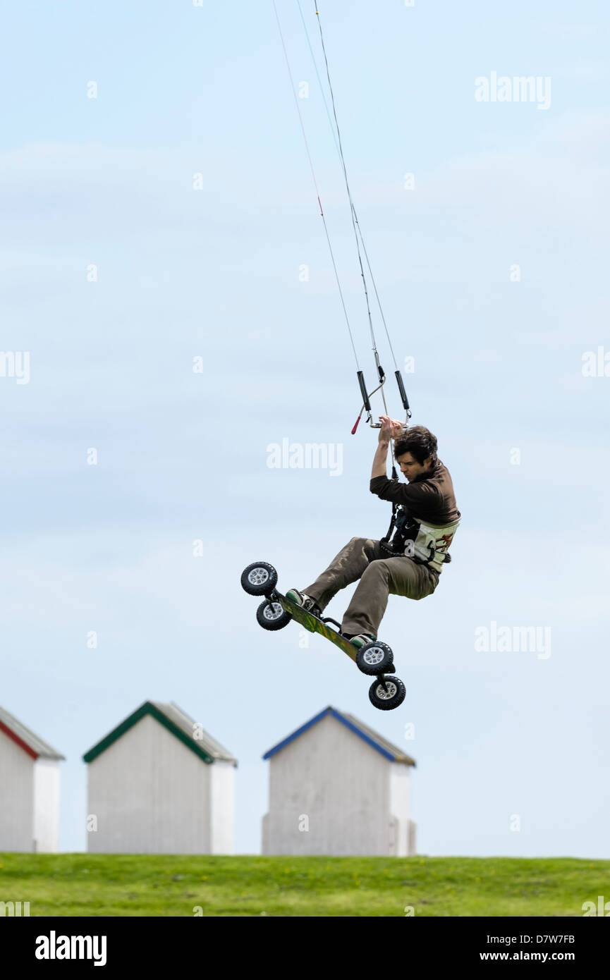 A land boarder performs tricks and jumps at Goring Gap, Worthing. Features Slight Blur due to speed of action - Stock Image