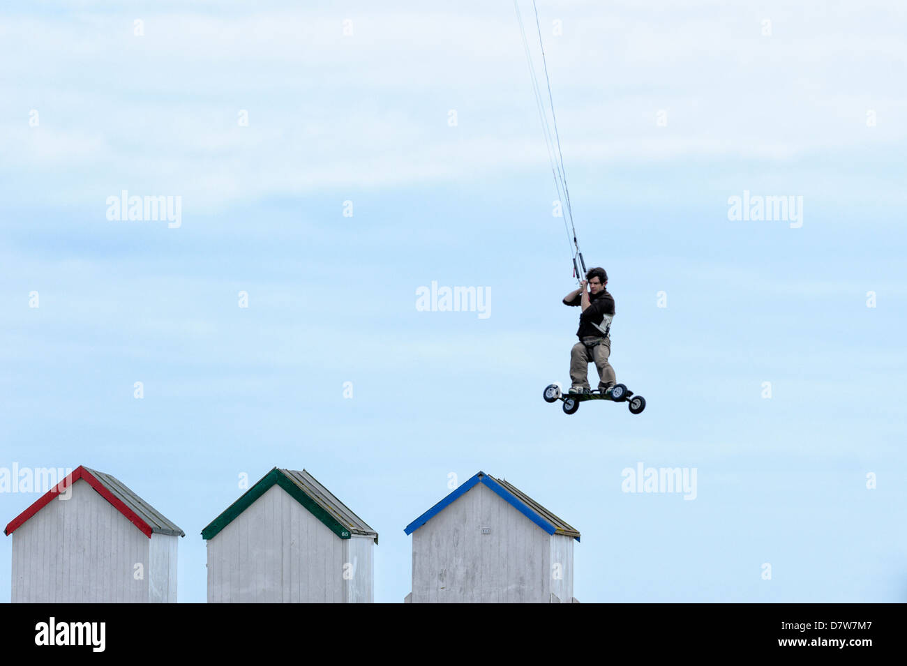 A Landboarder soars above beach huts at Goring Gap, Worthing. Picture by Julie Edwards - Stock Image