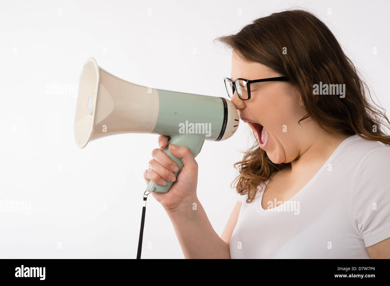 A young brunette teenage Caucasian girl shouting into a megaphone bull-horn wearing glasses yelling screaming uk - Stock Image