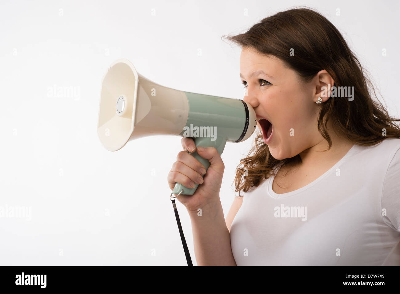 A young brunette teenage Caucasian girl shouting yelling screaming making loud noise into a megaphone bull-horn - Stock Image