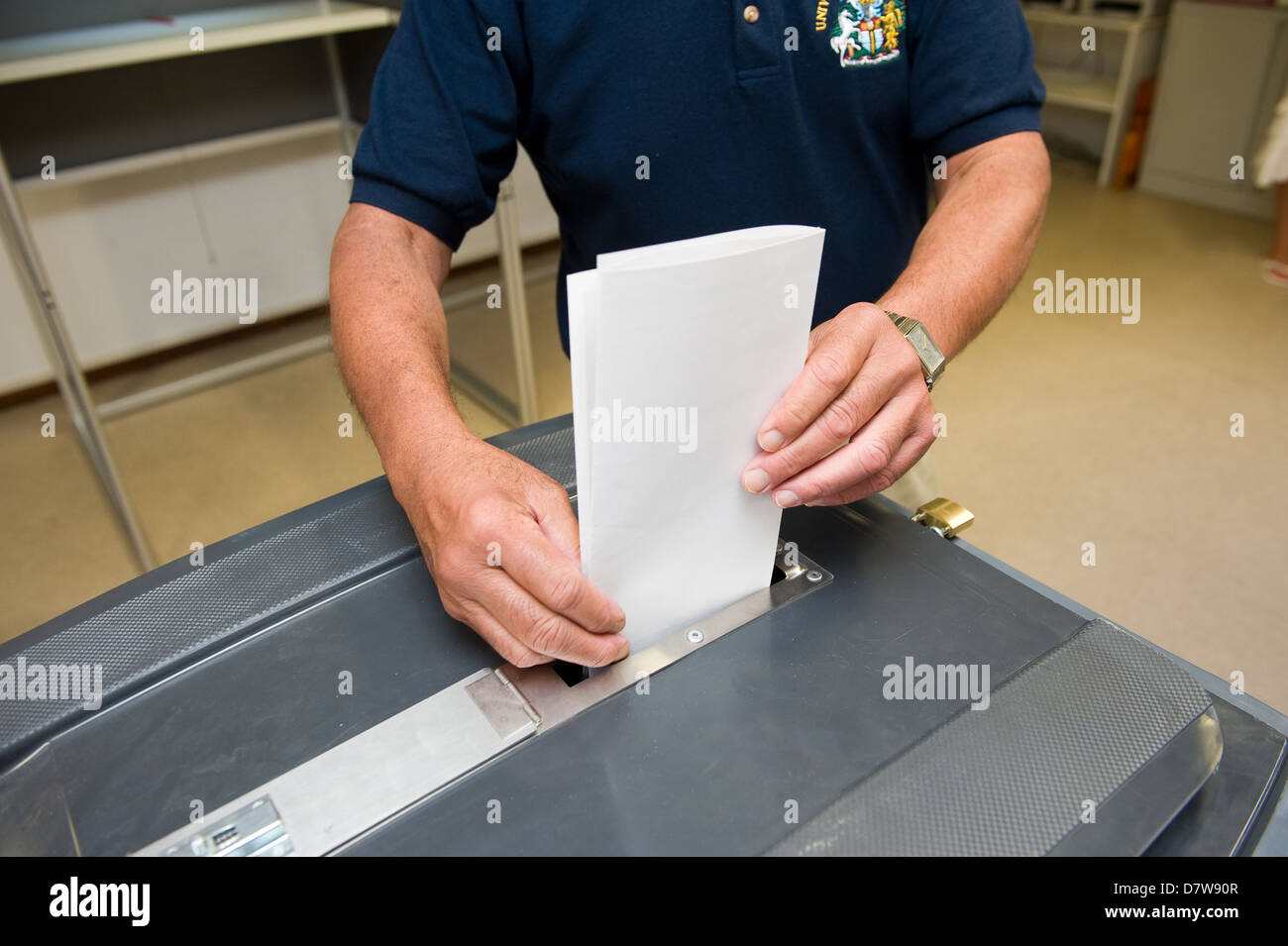 A man is putting his ballot in a ballot box - Stock Image