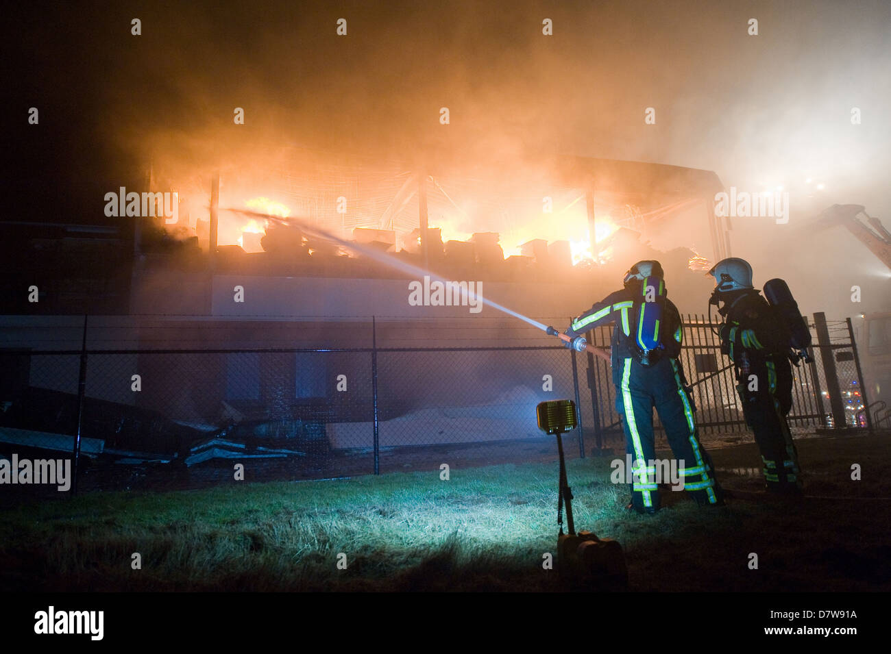Two firefighters are trying to extinguish a fire in a building - Stock Image