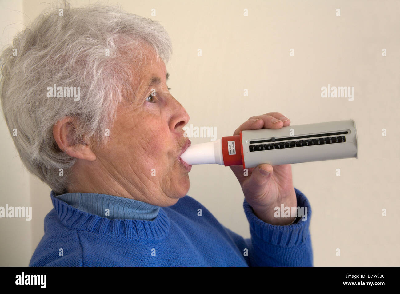 UK Elderly woman blowing into peak flow meter to monitor lung capacity - Stock Image